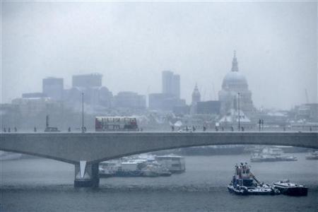 Commuters walk over Waterloo Bridge in the snow in central London January 21, 2013. REUTERS/Stefan Wermuth