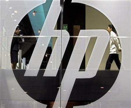 An employee walks past a Hewlett-Packard logo during the second day of the International Telecommunication Union (ITU) Telecom World 2006 in Hong Kong December 5, 2006. REUTERS/Paul Yeung/Files