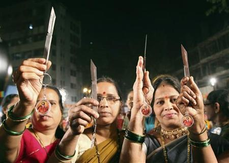 Women pose with knives, distributed by Shiv Sena, in Mumbai January 23, 2013. Picture taken January 23, 2013. REUTERS/Stringer