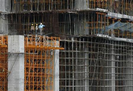 Workers stand at a construction site of a high rise building in Mumbai, September 9, 2009. REUTERS/ARKO DATTA/Files
