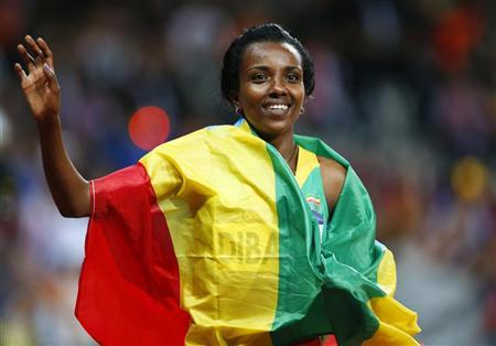 Ethiopia's Tirunesh Dibaba, with her national flag, waves after she won the women's 10,000m final at the London 2012 Olympic Games at the Olympic Stadium August 3, 2012. REUTERS/Mark Blinch