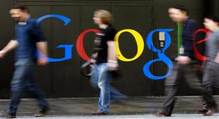 People walk past a logo next to the main entrance of the Google building in Zurich March 9, 2011. REUTERS/Arnd Wiegmann/Files