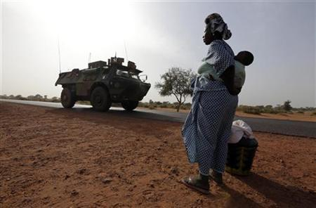 A woman looks at a French military vehicle drive past, as part of a convoy of French military vehicles including armored personnel carriers, jeeps and supply trucks, heading toward the recently liberated town of Diabaly January 24, 2013. REUTERS/Eric Gaillard