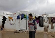 """Naciones Unidas instó el viernes a los países que limitan con Siria a mantener abiertas sus fronteras a los civiles que escapan del intenso conflicto en ese país y dijo que el éxodo de refugiados hacia Jordania era """"absolutamente dramático"""". En la imagen, un niño abrigado con una bufanda frente a una de las tiendas durante un tiempo frío en el campamento de refugiados Bab Al-Salam, en Azaz, cerca de la frontera sirio-turca, el 24 de enero de 2013. REUTERS/Zain Karam"""