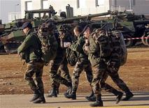 French soldiers, who prepare for their departure for Mali, walk past armoured vehicles with theirs belongings during a visit of the French Defence Minister at the military base of Miramas, southern France, January 25, 2013. REUTERS/Jean-Paul Pelissier (FRANCE - Tags: MILITARY POLITICS)