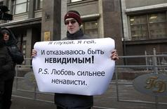 A gay rights activist holds a placard during a protest outside the Duma, Russia's lower house of Parliament, in Moscow January 25, 2013. REUTERS/Sergei Karpukhin