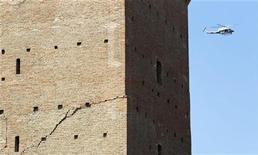 Un elicottero dei carabinieri sorvola una torre danneggiata dal recente terremoto a San Felice sul Panaro, vicino a Modena, il 30 maggio 2012. REUTERS/Giorgio Benvenuti