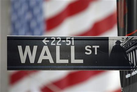 A sign for Wall Street is seen with a giant American flag in the background across from the New York Stock Exchange November 5, 2012. REUTERS/Chip East