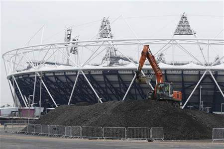 A digger operates in front of the Olympic Stadium, six months after the start of the London 2012 Olympic Games, in east London January 25, 2013. REUTERS/Olivia Harris