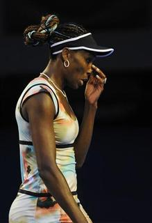 Venus Williams of the U.S. touches her nose during her women's singles match against Maria Sharapova of Russia at the Australian Open tennis tournament in Melbourne January 18, 2013. REUTERS/Toby Melville