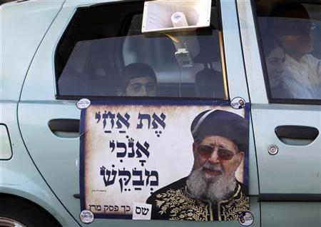 A boy looks out from a car covered with a sticker depicting Rabbi Ovadia Yosef, the spiritual leader of the ultra-Orthodox Shas party, in Jerusalem January 20, 2013. REUTERS/Ammar Awad