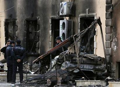 Policemen stand near a building of a local hotel, burnt down during recent mass protests, in the town of Ismailli, 200 km (125 miles) northwest of the capital Baku, January 25, 2013. REUTERS/David Mdzinarishvili