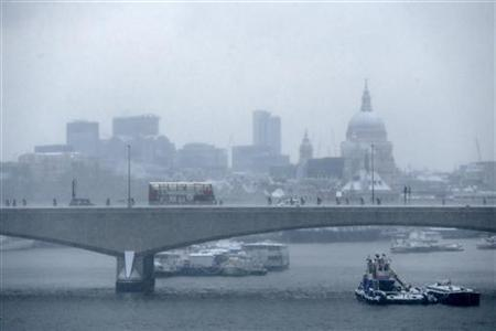 Commuters walk over Waterloo Bridge in the snow in central London January 21, 2013. REUTERS/Stefan Wermuth