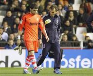 El portero y capitán del Real Madrid, Iker Casillas, estará fuera de los terrenos de juego durante 12 semanas tras ser operado por una fractura en la mano izquierda, dijo el viernes el cirujano que llevó a cabo la operación. Imagen de Casillas (izq.) dejando el campo tras sufrir la lesión en el partido de Copa del Rey contra el Valencia disputado el 23 de enero en Mestalla. REUTERS/Heino Kalis