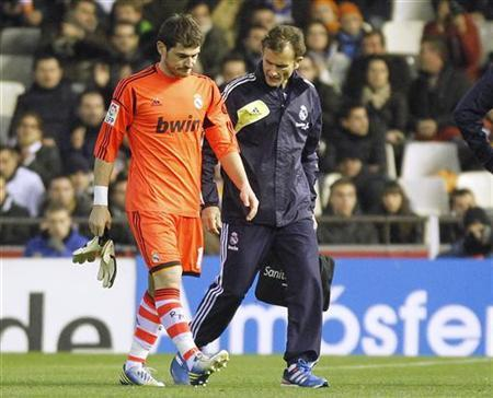 Real Madrid's goalkeeper Iker Casillas (L) leaves the pitch after injuring his hand during their Spanish King's Cup quarter-final second leg soccer match against Valencia at the Mestalla stadium in Valencia, January 23, 2013. REUTERS/Heino Kalis