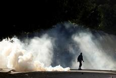 Protesters are seen through tear gas used by police during clashes in Alexandria, January 25, 2013. Youths fought Egyptian police in Cairo and Alexandria on Friday on the second anniversary of the revolt that toppled Hosni Mubarak and brought the election of an Islamist president who protesters accuse of riding roughshod over the new democracy. REUTERS/Asmaa Waguih