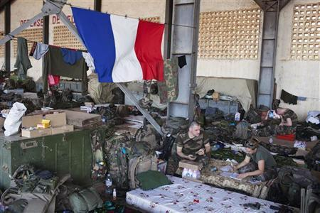 French soldiers talk under a French flag in a hangar at the Malian army air base in Bamako January 14, 2013. REUTERS/Joe Penney