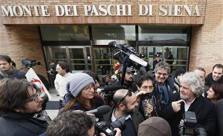Five-Star Movement activist and comedian Beppe Grillo (R) talks to the media as he leaves the shareholders meeting at Banca Monte dei Paschi in Siena, January 25, 2013. REUTERS/Stefano Rellandini