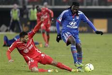 Le Valenciennois Lindsay Rose (à gauche) à la lutte avec le Lyonnais Bafétimbi Gomis, qui a marqué vendredi son 12e but en championnat. L'OL a repris vendredi soir trois points d'avance sur le Paris Saint-Germain en tête de la Ligue 1 à la faveur d'une victoire autoritaire (2-0) au Stade du Hainaut en match avancé de la 22e journée. REUTERS/Pascal Rossignol (FRANCE - Tags: SPORT SOCCER)