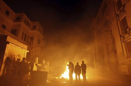 Protesters opposing Egyptian President Mohamed Mursi stand near a fire as they take cover from tear gas fired by riot police during clashes along Mohamed Mahmoud street near Tahrir Square in Cairo January 25, 2013. REUTERS/Amr Abdallah Dalsh