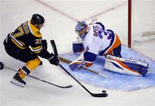 Boston Bruins' center Patrice Bergeron (L) scores a goal against New York Islanders' goaltender Rick DiPietro in the third period of their NHL hockey game in Boston, Massachusetts January 25, 2013. REUTERS/Brian Snyder
