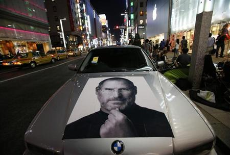 A portrait of Apple co-founder Steve Jobs is seen on a BMW car near people waiting for the release of iPhone 5 in front of Apple Store Ginza in Tokyo September 20, 2012. REUTERS/Toru Hanai