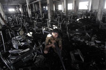 A man inspects the burnt interior of a garment factory after a fire in Dhaka January 26, 2013. REUTERS/Andrew Biraj