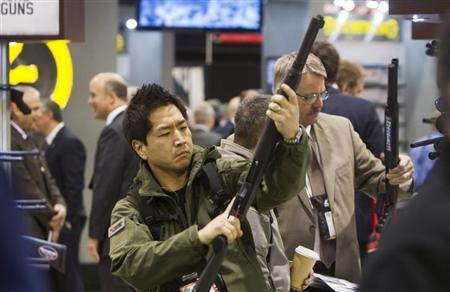 Paul Hwang of Auburn, Washington, looks over a Mossberg shotgun during the annual SHOT (Shooting, Hunting, Outdoor Trade) Show in Las Vegas January 15, 2013. REUTERS/Las Vegas Sun/Steve Marcus