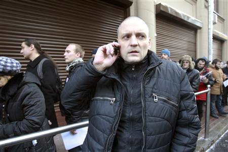 Sergei Udaltsov, leader of the Left Front opposition party, speaks on a telephone after handing petitions to the Presidential reception in Moscow January 26, 2013. REUTERS/Sergei Karpukhin