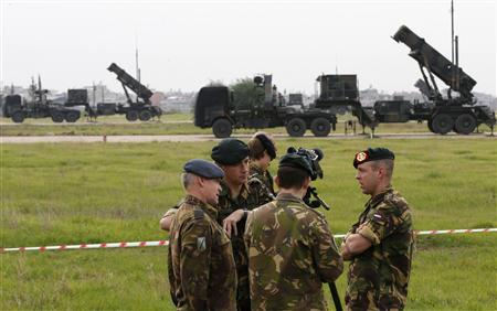 Dutch soldiers, with the Patriot system in the background, chat during media day at a military airbase in Adana, southern Turkey, January 26, 2013. REUTERS/Murad Sezer
