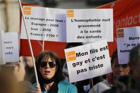 A woman walks near signs which support same-sex marriage and in support of the government's draft law to legalise marriage and adoption for same-sex couples, in Nantes, western France, December 15, 2012. Sign at top right reads, ''Homophobia is dangerous to the health of children''; and the sign below reads, ''My son is gay, and this is not sad''. REUTERS/Stephane Mahe