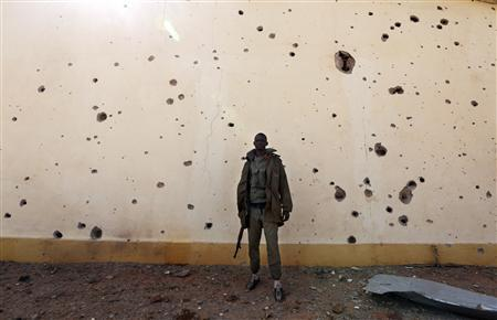 A Malian soldier stands near a wall with bullet holes in the recently liberated town of Konna January 26, 2013. REUTERS/Eric Gaillard