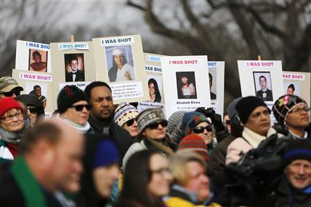 People hold signs memorializing shooting death victims as they participate in the March on Washington for Gun Control on the National Mall in Washington, January 26, 2013. REUTERS/Jonathan Ernst