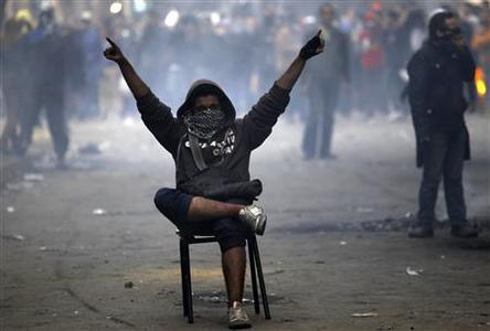 A protester opposing Egyptian President Mohamed Mursi gestures at riot police during clashes along Mohamed Mahmoud street which leads to the Interior Ministry, near Tahrir Square in Cairo January 26, 2013. REUTERS/Amr Abdallah Dalsh