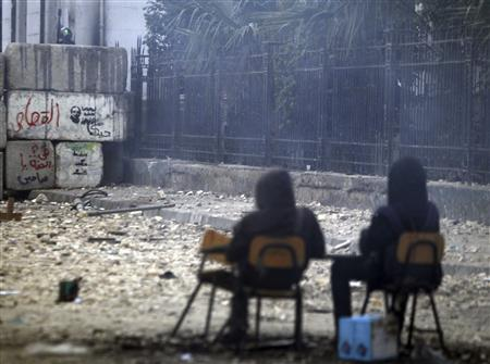A riot policeman (L) releases tear gas towards protesters opposing Egyptian President Mohamed Mursi as they sit on chairs during clashes along Mohamed Mahmoud street which leads to the Interior Ministry, near Tahrir Square in Cairo January 26, 2013. REUTERS/Amr Abdallah Dalsh