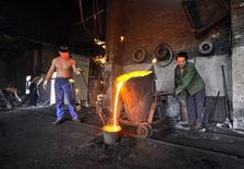 Labourers pour molten iron into a container at a foundry in Xiangfan, Hubei province July 2, 2010. REUTERS/Stringer