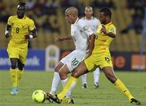L'Algérien Sofiane Feghouli (à gauche) lutte pour la conquête du ballon avec le Togolais Alaixys Romao lors du match de la Coupe d'Afrique des nations (Can) remporté 2-0 par le Togo. Ce résultat signifie que l'Algérie est le premier pays à être éliminé de la Can 2013 qui se dispute en Afrique du Sud. /Photo prise le 26 janvier 2013/REUTERS/Ihsaan Haffejee