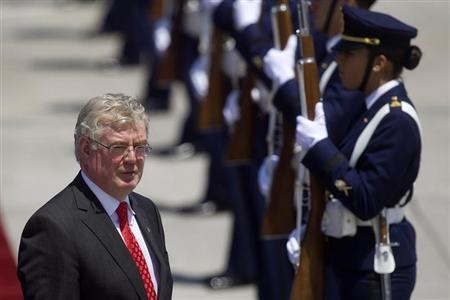 Irish Foreign Minister Eamon Gilmore walks past the honour guard as he arrives to attend the summit of the Community of Latin American, Caribbean States and European Union (CELAC-UE), at the airport of Santiago January 25, 2013. REUTERS/Claudio Reyes
