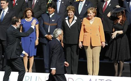 Spain's Prime Minister Mariano Rajoy (L) waves to Costa Rica's President Laura Chinchilla (2nd L-R), Bolivia's President Evo Morales, Brazil's President Dilma Rousseff, Germany's Chancellor Angela Merkel and Argentina's President Cristina Fernandez, before an official photo at the summit of the Community of Latin American, Caribbean States and European Union (CELAC-UE) in Santiago January 26, 2013. REUTERS/Eliseo Fernandez