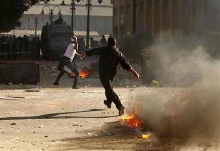 A protester throws stones at police as another prepares to throw a burning tyre during clashes in Alexandria, January 25, 2013. REUTERS/Asmaa Waguih