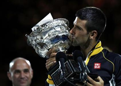 Former tennis player Andre Agassi of the U.S. looks on as Novak Djokovic of Serbia kisses the Norman Brookes Challenge Cup after he defeated Andy Murray of Britain in their men's singles final match at the Australian Open tennis tournament in Melbourne, January 27, 2013. REUTERS/Daniel Munoz