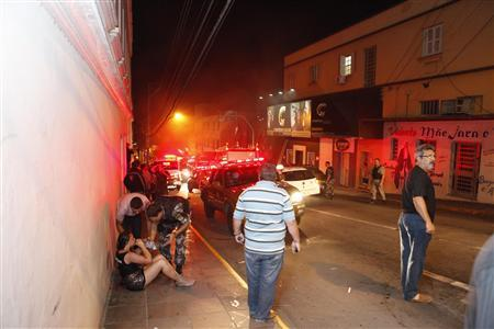 A police officer helps a woman next to Kiss nightclub in the southern city of Santa Maria, 187 miles (301 km) west of the state capital of Porto Alegre, in this picture taken by Agencia RBS, January 27, 2013. REUTERS-Germano Roratto-Agencia RBS