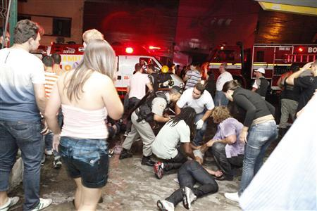 A policeman and rescue workers help a man in front of Kiss nightclub in the southern city of Santa Maria, 187 miles (301 km) west of the state capital of Porto Alegre, in this picture taken by Agencia RBS, January 27, 2013. REUTERS-Germano Roratto-Agencia RBS