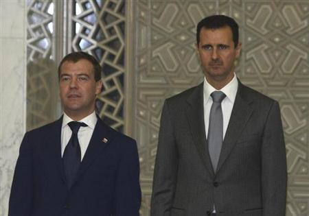 Russia's Dmitry Medvedev and Syria's President Bashar al-Assad (R) pose for photos as they arrive for a news conference after a meeting in Damascus May 11, 2010. REUTERS/Khaled al-Hariri/Files