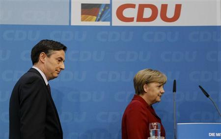 German Chancellor Angela Merkel and Lower Saxony federal state premier McAllister leave a news conference at the headquarters of Merkel's Christian Democratic Union party CDU in Berlin January 21, 2013. REUTERS/Wolfgang Rattay