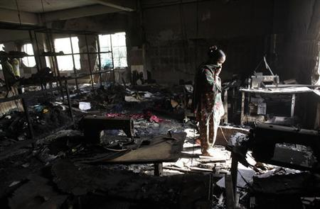 A worker visits a burnt garment factory after a fire which killed more than a hundred people, in Savar November 26, 2012. REUTERS/Andrew Biraj