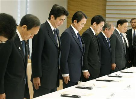 Japan's Prime Minister Shinzo Abe (3rd L) and his cabinet ministers pay silent tribute to victims who were killed in the hostage crisis in Algeria, during an emergency meeting on the hostage crisis at Abe's official residence in Tokyo, in this photo taken by Kyodo January 25, 2013. REUTERS/Kyodo