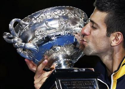 Novak Djokovic of Serbia kisses the Norman Brookes Challenge Cup after defeating Andy Murray of Britain in their men's singles final match at the Australian Open tennis tournament in Melbourne, January 27, 2013. Djokovic became the first man to win three successive Australian Open titles in the professional era. REUTERS/Damir Sagolj