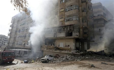 A man tries to extinguish a fire after a Syrian Air force air strike in Ain Tarma neighbourhood of Damascus January 27, 2013. REUTERS/Goran Tomasevic