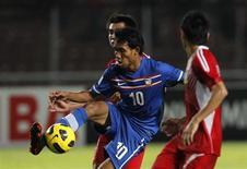 El delantero taliandés Teerasil Dangda espera que entrenar con la estrella del Atlético de Madrid Radamel Falcao pueda ayudarle a lograr su objetivo de jugar algún día en Europa. En la imagen, el tailandés Teerasil (centro) durante un partido internacional en diciembre de 2010. REUTERS/Beawiharta